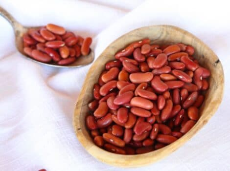 Square Crop - wooden dish of dried Kidney Beans on a white cloth background, spoon of beans in background.