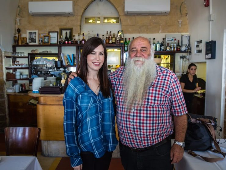 Photograph of a man with a long white beard and a brunette woman. They are Tori Avey and Chef Uri Jeremias.