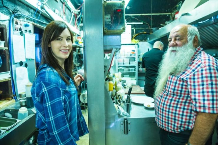 A man with a white beard (Chef Uri Jeremias) and a brunette woman (Tori Avey) in a restaurant kitchen.