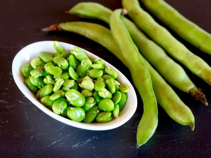 A white dish with fresh green fava beans next to 5 fava bean pods on a black background.