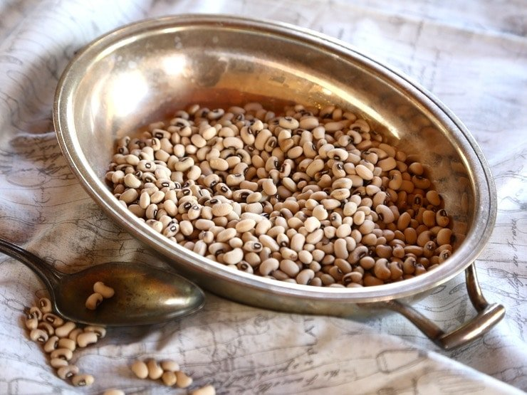 Dried black-eyed peas in a metal bowl next to a spoon on a white cloth background.