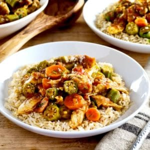 Close up of Chicken Okra Stew on a bed of rice in a white bowl on a wooden background, two bowls of stew and wooden spoon in background.