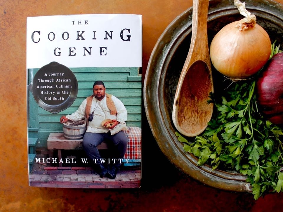 A copy of the book The Cooking Gene by Michael Twitty sits next to to a bowl filled with cilantro, a red onion, a brown onion, and a wooden spoon.