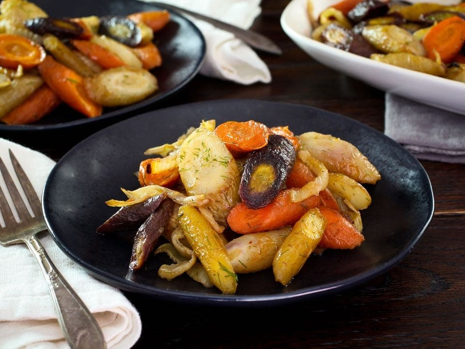 A pile of roasted carrots and fennel on a black plate next to a fork sitting on a white napkin.
