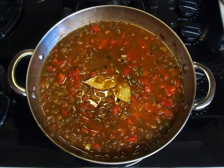 Sauce simmering with bay leaves on stovetop.