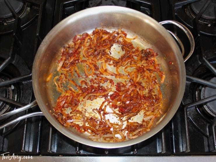 Sautéing onion and tomato paste to make mnazaleh, a traditional Middle Eastern Druze recipe.