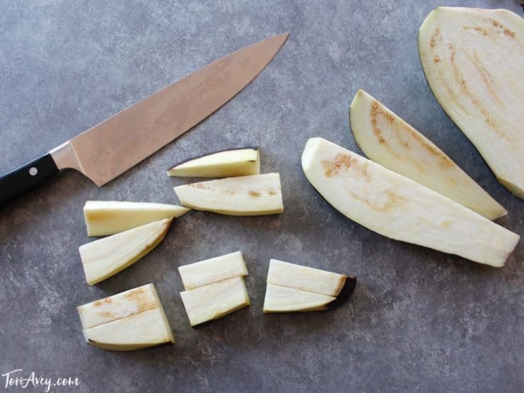 Eggplant cut into chunks with chef's knife on concrete background.