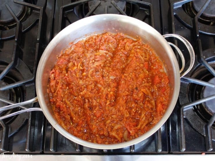 Tomato reduction sauce in saute pan on stovetop.
