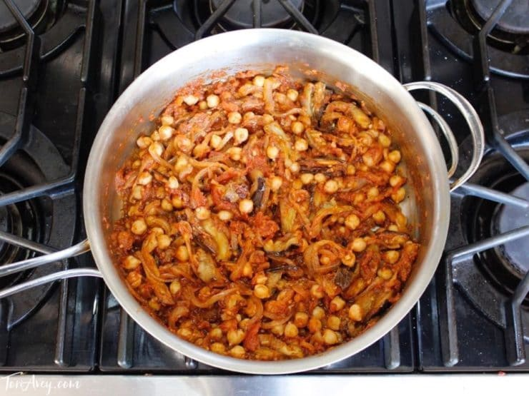 Mnazaleh cooking in saute pan with chickpeas and eggplant pieces.