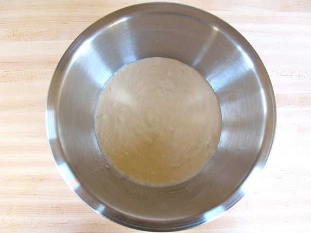 Stainless steel bowl of batter on a light wood background.