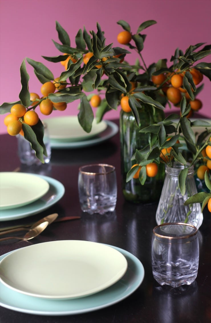 Table setting - plates, utensils and glass with gold accent. Clear vase with kumquat branch centerpiece.