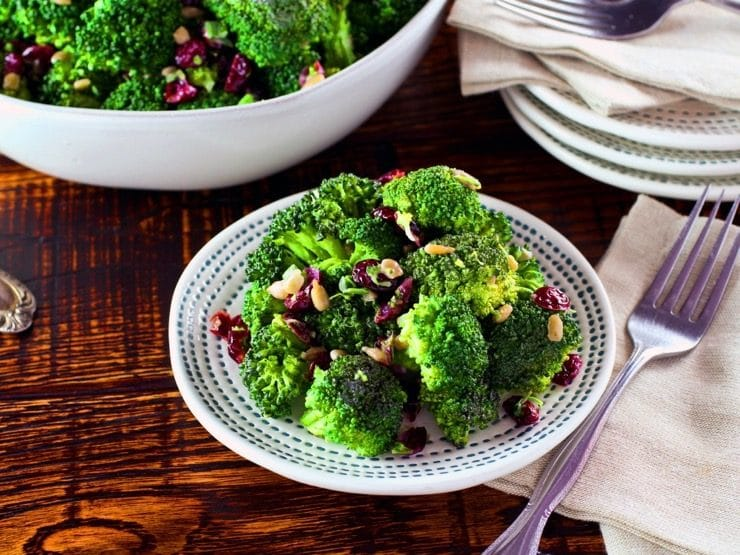 A plate of broccoli salad next to a fork and napkin on a wooden table. In the background is a large bowl of additional broccoli salad.