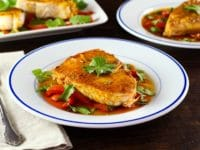 Moroccan paprika fish on a bed of vegetables topped wth fresh green herbs in a white bowl.