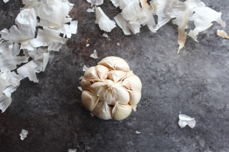 Whole head of garlic with whole cloves, outer papery layers of skin removed.