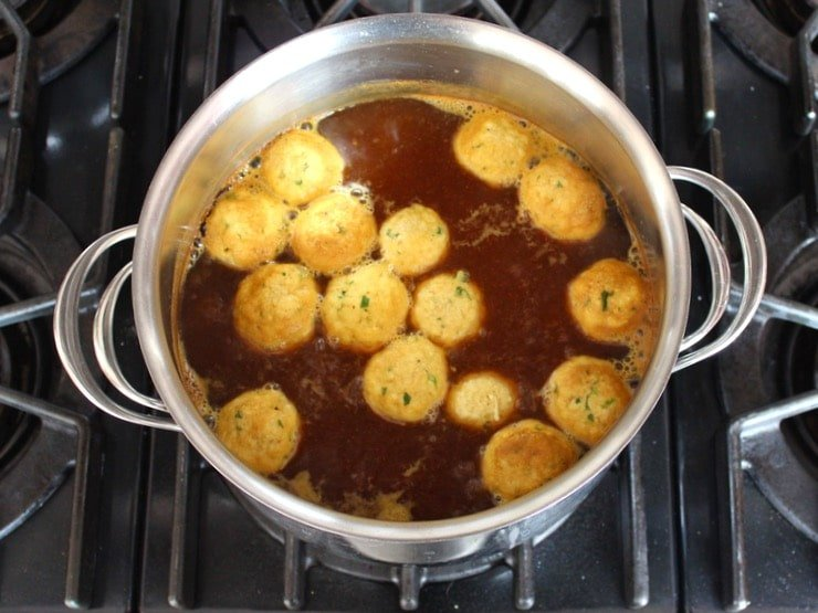 Matzo balls cooking in a large pot of broth.