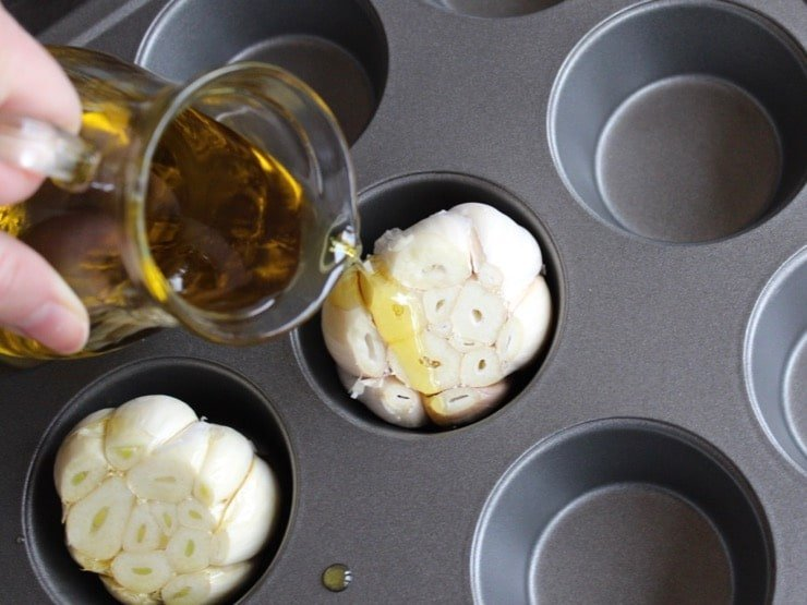 Small carafe drizzling olive oil on top of whole garlic head with exposed cloves in muffin pan.