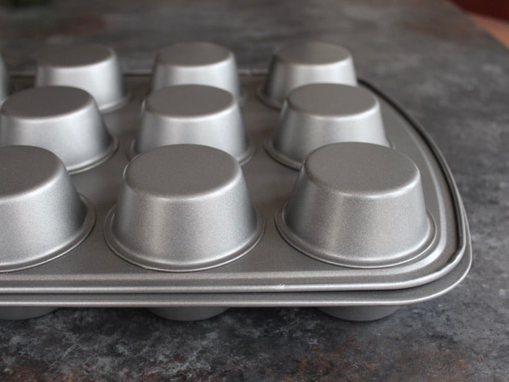 Two muffin tins, one inverted on top of the other, on grey countertop.