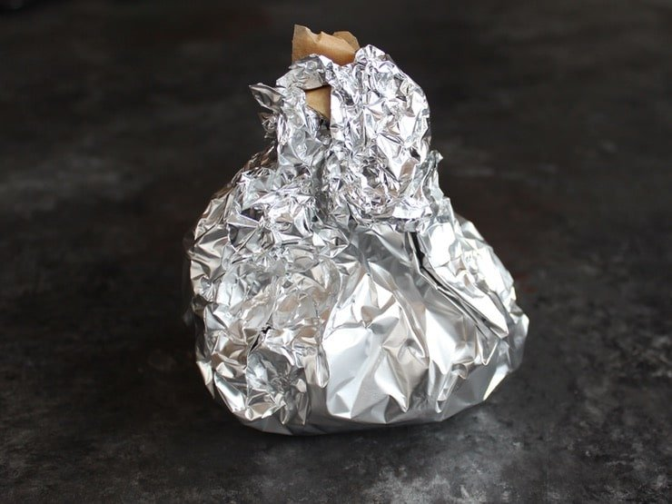 Garlic head wrapped up in foil and parchment packet.