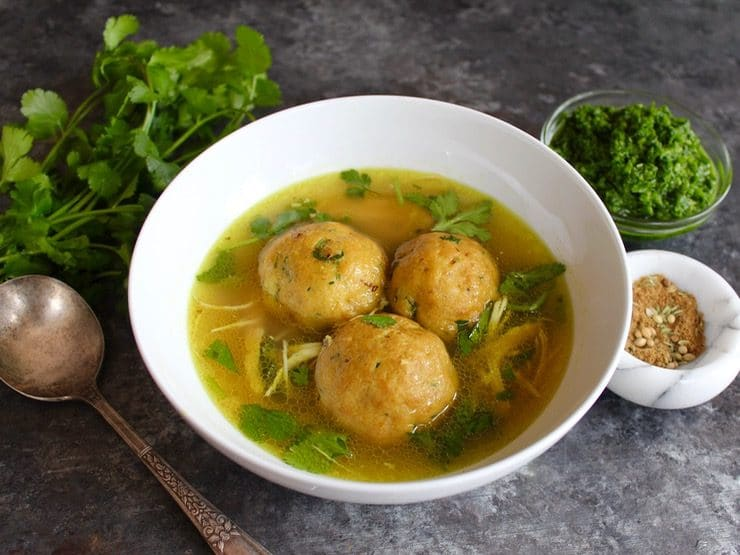Yemenite matzo ball soup with three large matzo balls in a white bowl on a silver tray.