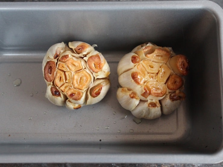 Two heads of roasted garlic with exposed cloves in small baking pan.