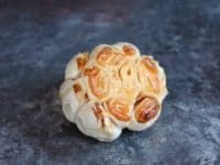 Head of roasted garlic with exposed cloves on grey countertop.