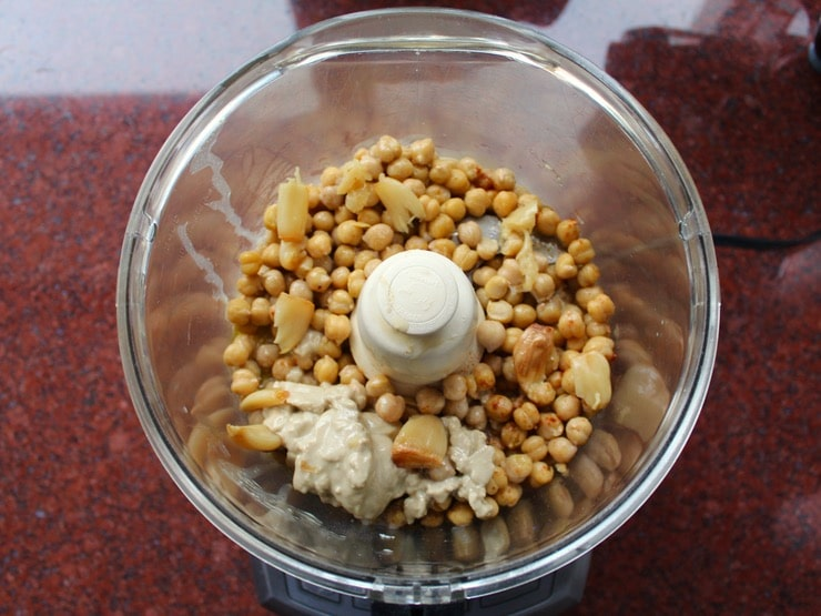 Hummus ingredients combined in food processor ready to blend - chickpeas, tahini, roasted garlic, spices, salt.