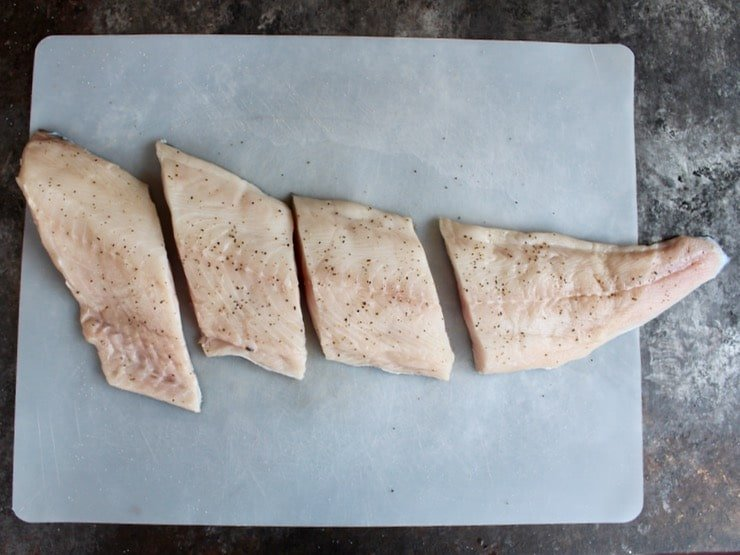 Long fresh cod fillet on cutting board, seasoned with salt and pepper, sliced into 4 pieces