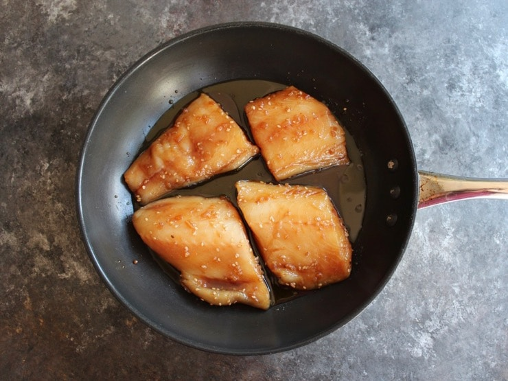 Four marinated Teriyaki Black Cod fillets, uncooked, in a skillet with olive oil on countertop.