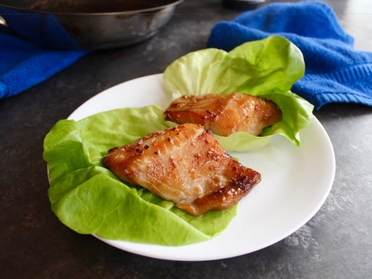 Close up on two Teriyaki Black Cod fillets, broiled and browned, on lettuce leaves on a white plate.