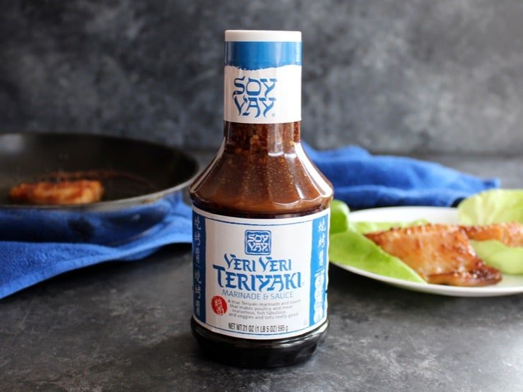 Bottle of Soy Vay Veri Veri Teriyaki Marinade and Sauce, fish and skillet in background with blue towel.