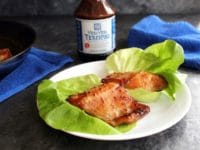 Two pieces of glazed broiled Teriyaki Black Cod in foreground, bottle of Soy Vay Veri Veri Teriyaki Marinade and Sauce in background with blue towel and skillet.
