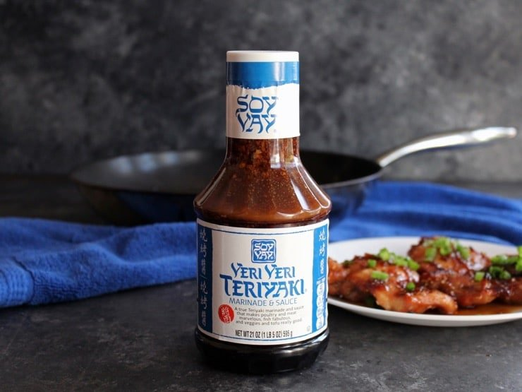 Bottle of Soy Vay Veri Veri Teriyaki Marinade on countertop with plate of Spicy Teriyaki Broiled Chicken Thighs topped with scallions in background, and skillet on blue towel.