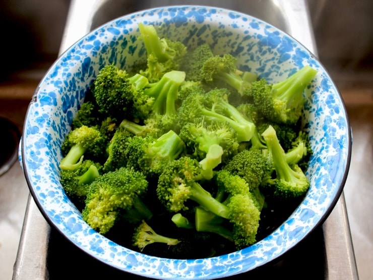 Steamed broccoli in blue speckled colander in stainless steel sink.