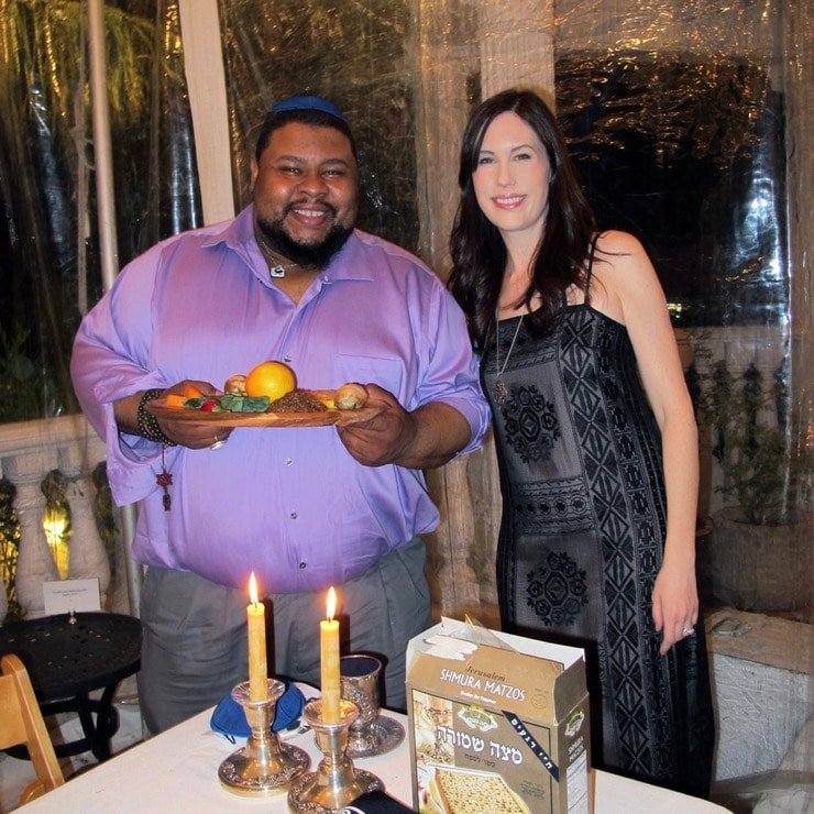 Michael Twitty and Tori Avey at Passover Seder 2017 - Michael holding African American Seder Plate, candles and matzo on table in foreground.