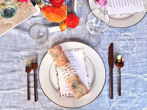 Overhead shot of table setting for Passover Seder - matzo napkin ring and matzo-backed menu on plate with cloth napkin, gold utensils, wine glass and flowers.