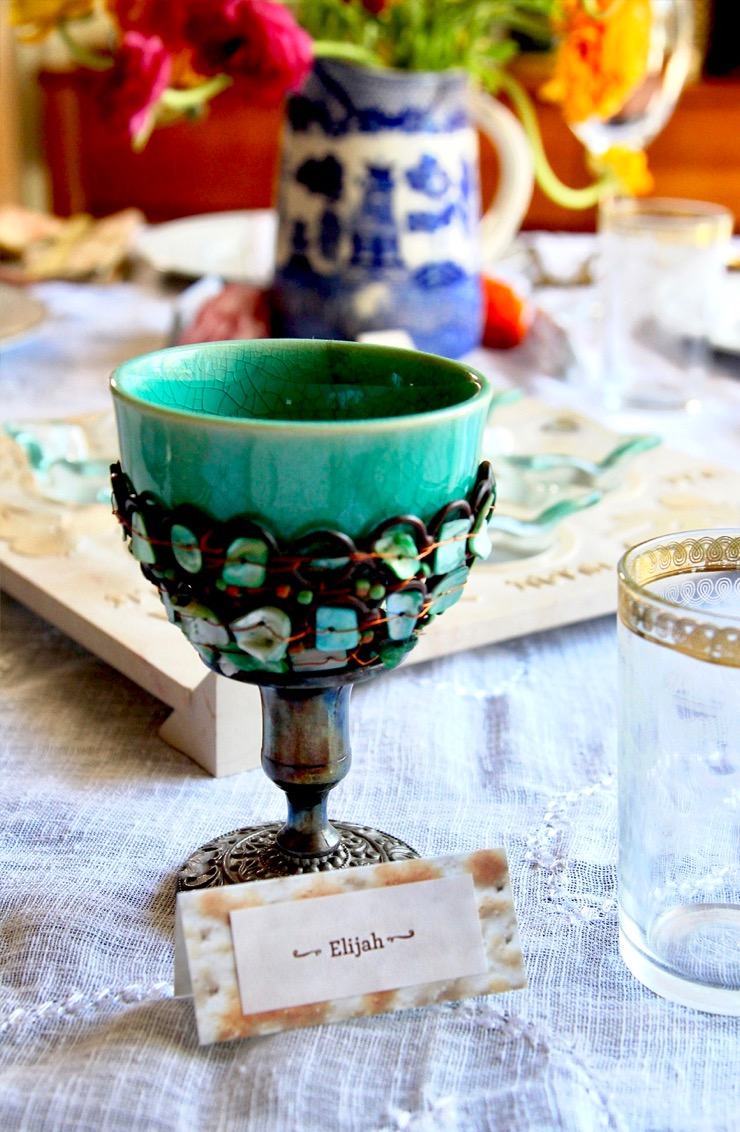 A turquoise Elijah cup sitting on a table decorated for the Passover seder.