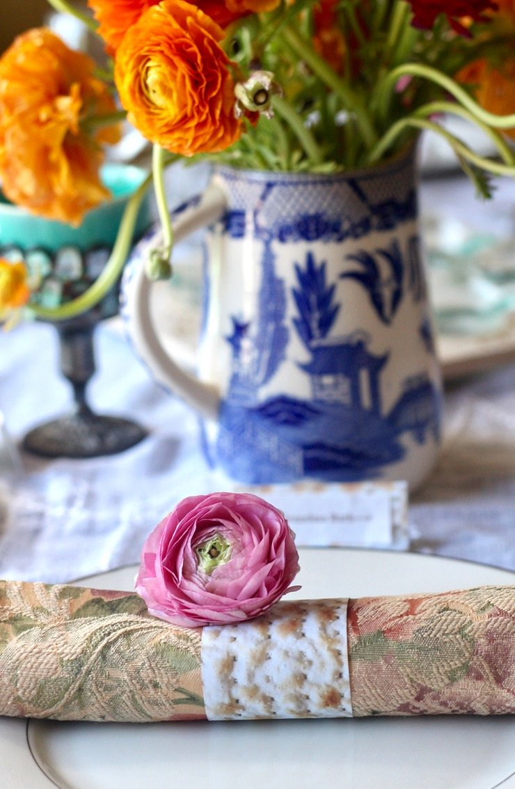 A pink ranunculus sits at the edge of a decorated Passover seder table. Behind the ranunculus is a blue and white vase and an Elijah cup.