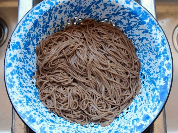 Cooked soba noodles in blue speckled colander in sink
