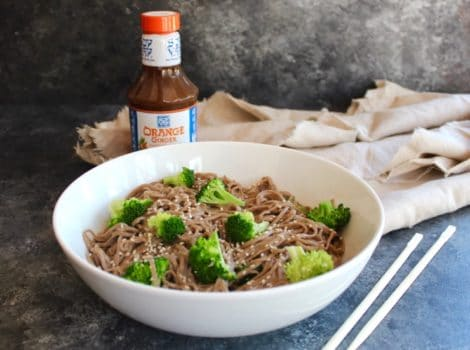 Bowl of soba noodles with broccoli and creamy dressing with chopsticks in foreground, bottle of Soy Vay marinade in background with cloth.