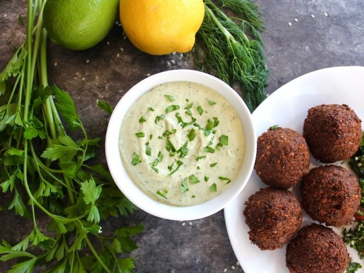 White bowl of herb tahini sauce topped with chopped fresh parsley alongside a falafel plate, fresh parsley, fresh dill, lemon and lime on the side.