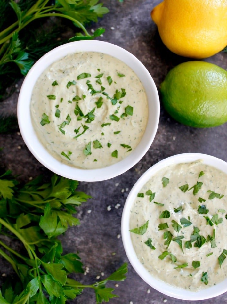 Two white bowls of herb tahini sauce topped with chopped parsley on concrete background with fresh parsley, lemon, lime and sesame seeds.