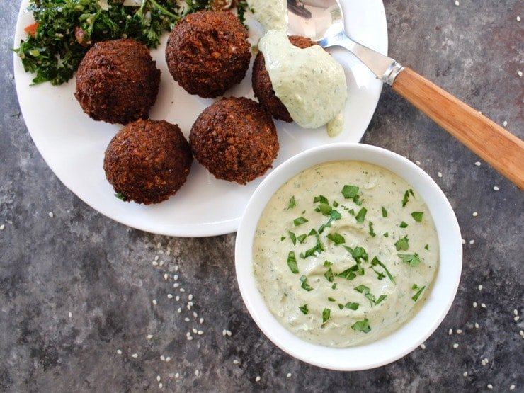 White bowl of herb tahini sauce topped with chopped fresh parsley alongside a falafel plate. One piece of falafel topped with tahini sauce, spoon beside it. Tabouli salad in background.