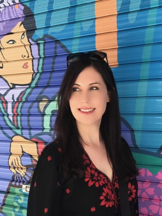 Tori Avey in Japan in front of a colorful wall painted with a Geisha.