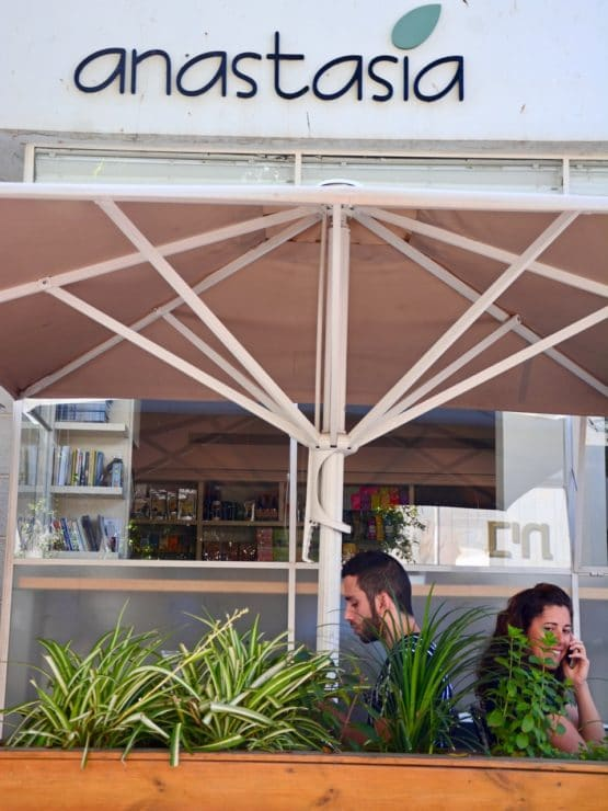 Front of Anastasia restaurant in Tel Aviv, two people dining under outdoor umbrella.