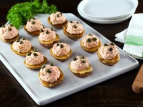 Overhead view of a tray of small roasted potatoes topped with a lox topping and garnished with capers