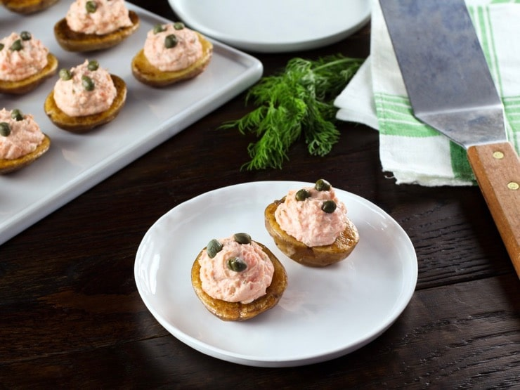 Small roasted potatoes topped with a lox topping and garnished with capers on a white plate.