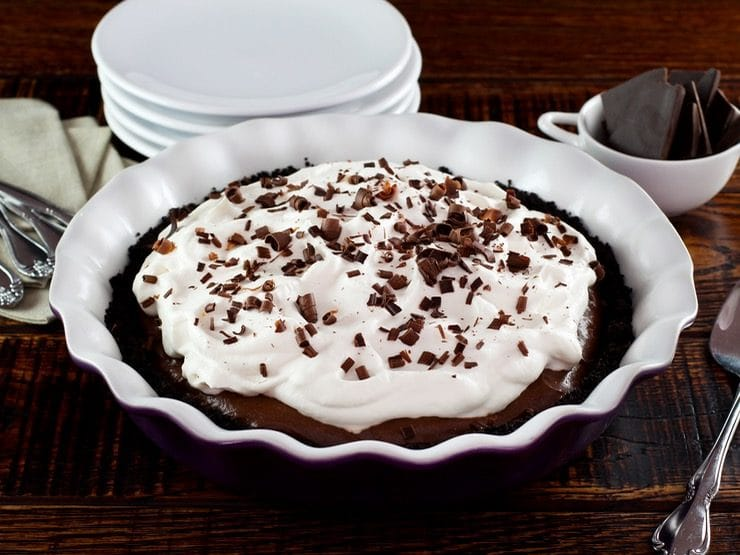 A whole pie topped with fluffy white whipped cream and brown chocolate shavings.