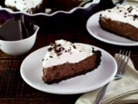 Slice of chocolate pie topped with whipped cream and chocolate shavings on a white plate.