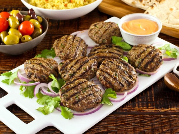 White platter of Middle Eastern Burgers char-grilled on a bed of purple onion rings and herbs, with spicy sriracha mayo sauce on the side, dish of yellow couscous, pita bread and olives in background.