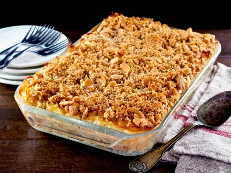 A large glass casserole dish filled with noodle kugel with a crunch cookie topping.